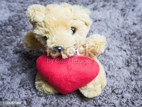 Soft toy fluffy bear with a heart sitting on carpet
