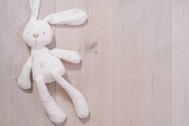 juguete suave en forma de conejo sobre fondo de madera - foto de stock