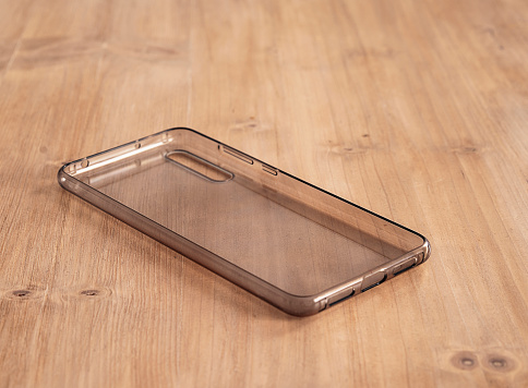 Soft transparent mobile case in a light wood table