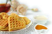 Soft waffles in the shape of a heart in a white plate on a white background close-up, selective focus.