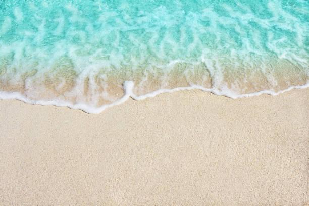 Soft wave of blue ocean on sandy beach stock photo