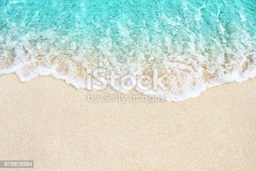 Soft blue ocean wave on sandy beach. Background.