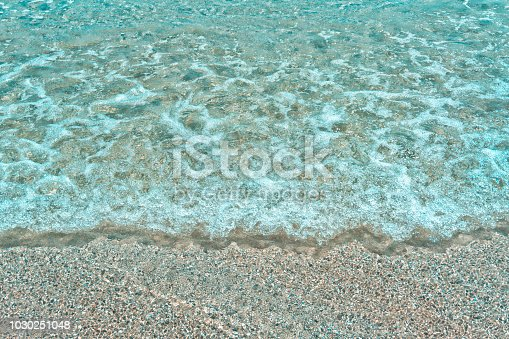 969085876 istock photo Soft wave of turquoise sea water on the sandy beach. Close-up and directly above photographed 1030251048