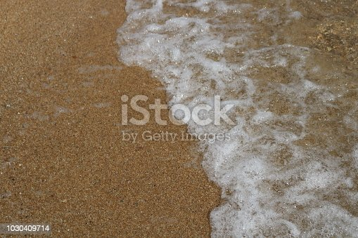 istock Soft wave of turquoise sea water on the sandy beach. Close-up and directly above photographed 1030409714