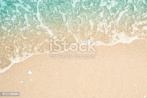 istock Soft wave of turquoise sea water on the sandy beach. Close-up and directly above photographed. 912159594