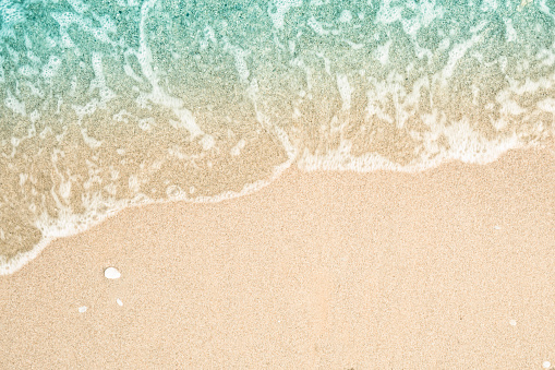 Soft wave of turquoise sea water on the sandy beach. Close-up and directly above photographed.