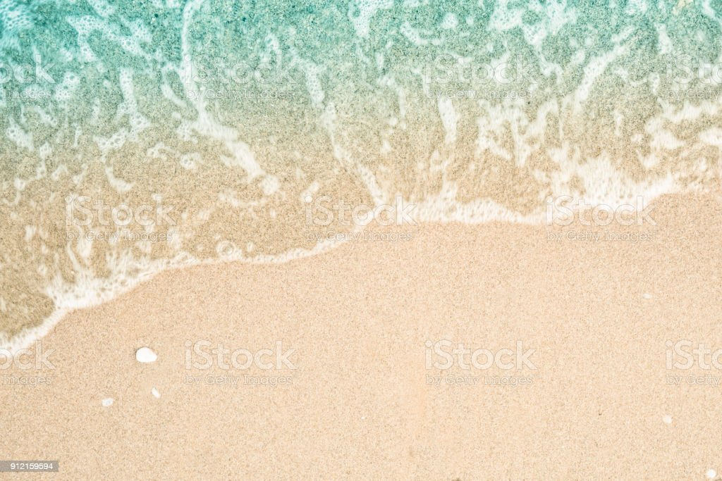 Soft wave of turquoise sea water on the sandy beach. Close-up and directly above photographed. - foto stock