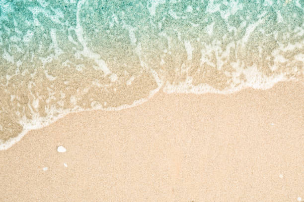 Soft wave of turquoise sea water on the sandy beach. Close-up and directly above photographed. stock photo