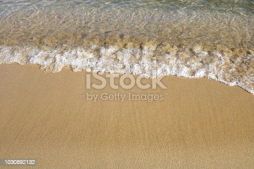istock Soft wave of turquoise sea water on the sandy beach. 1030892132