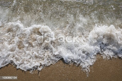 969085876 istock photo Soft wave of turquoise sea water on the sandy beach. 1030892134