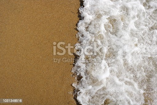 istock Soft wave of turquoise sea water on the sandy beach. 1031348516