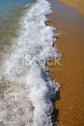 istock Soft wave of turquoise sea water on the sandy beach. 1031351002