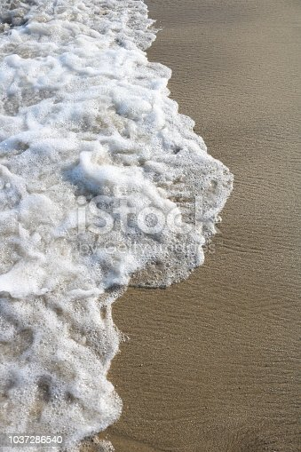 istock Soft wave of turquoise sea water on the sandy beach. 1037286540