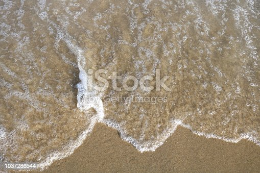istock Soft wave of turquoise sea water on the sandy beach. 1037286544
