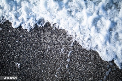 istock Soft wave of turquoise sea water on the sandy beach 1054635676