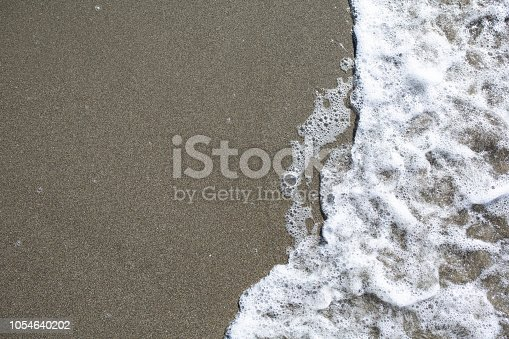 istock Soft wave of turquoise sea water on the sandy beach 1054640202