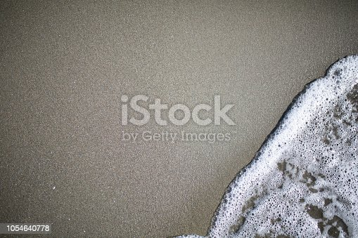istock Soft wave of turquoise sea water on the sandy beach 1054640778