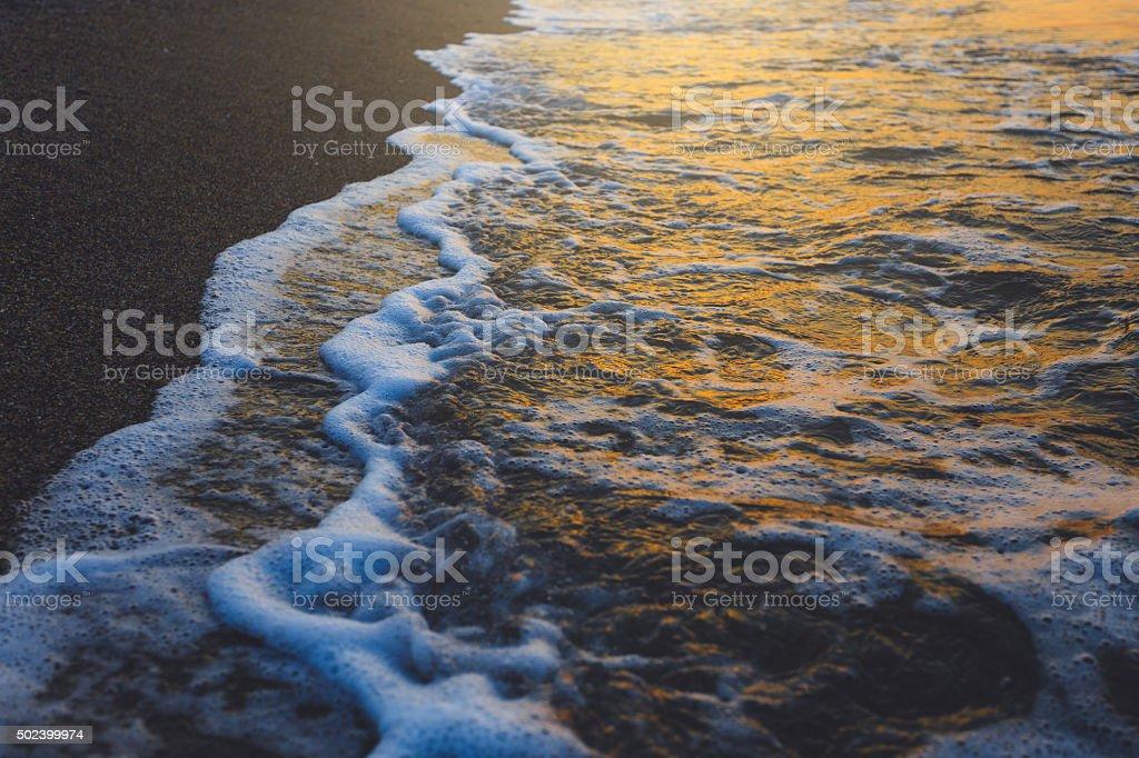 Weiche Welle bei Sonnenuntergang am Strand, die goldenen Farben – Foto