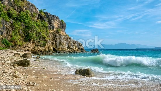 Motion blurred waves breaking on a secluded rocky beach, with a dramatic cliff and blue sky in the background, in a tropical resort area in Oriental Mindoro Province on Mindoro Island.