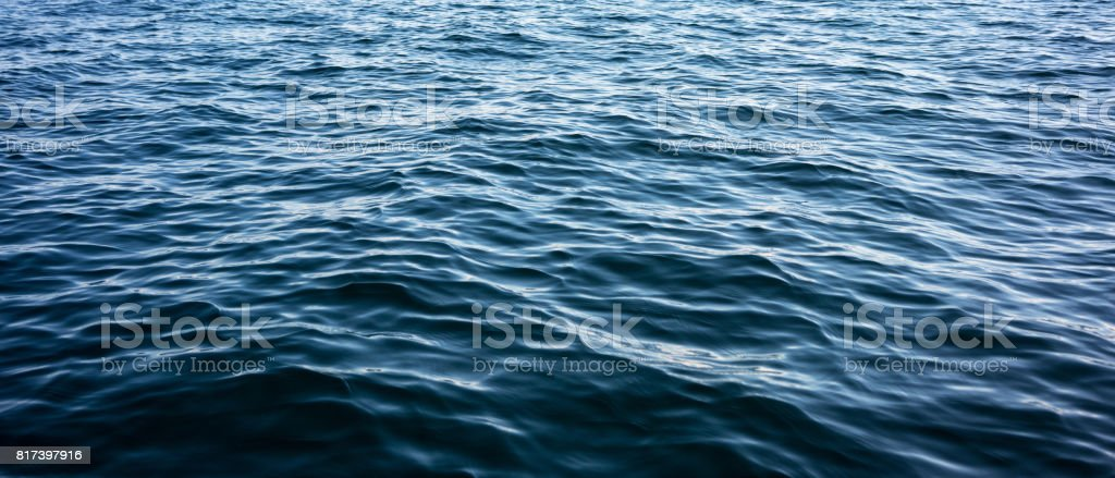 Soft waves on dark ocean surface stock photo