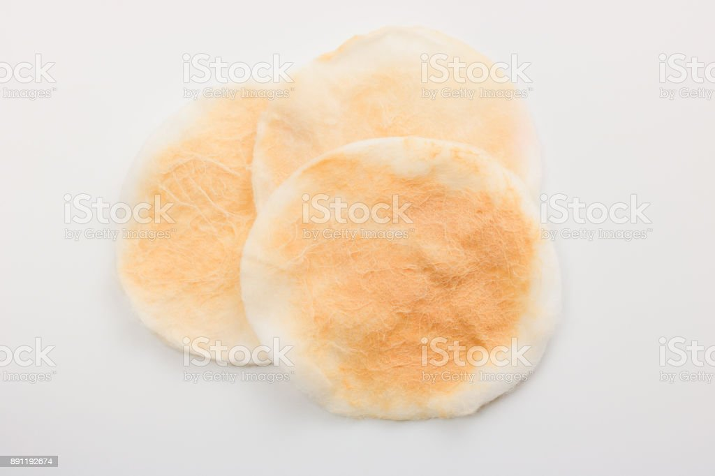 Soft white cosmetic cotton pad after used for makeup remover, Isolated on white background, Close up, Top view. stock photo