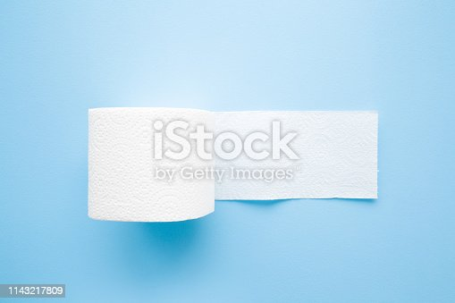 istock Soft, white toilet paper roll on light pastel blue background. Hygiene concept. Empty place for text or logo. Closeup. Top view. 1143217809