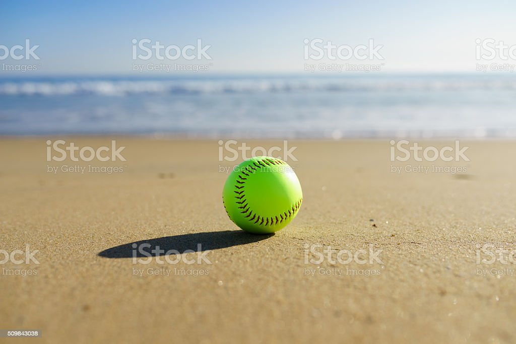 Softball at a California beach with white wave in pacific ocean with...