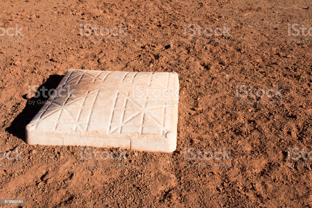 Softball base in the dirt stock photo