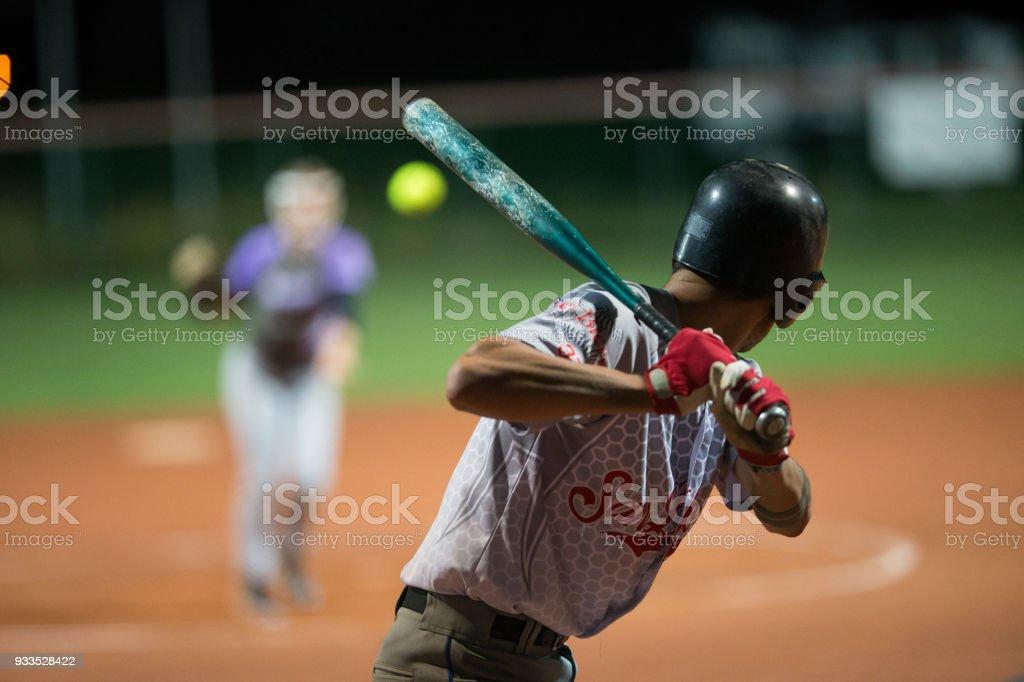 空中のボールをヒットする準備をしてソフトボール打者 ストックフォト
