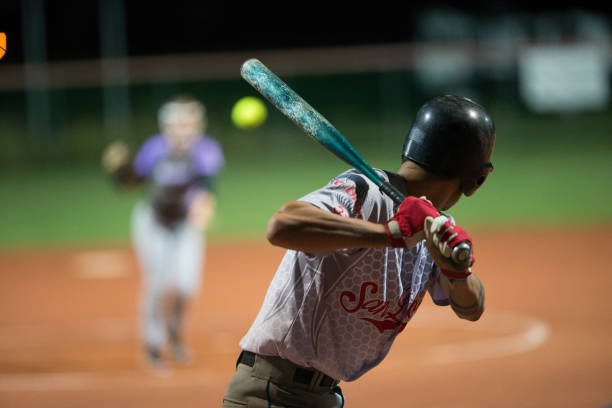 softball batter preparing to hit the ball mid air - softball stock photos and pictures
