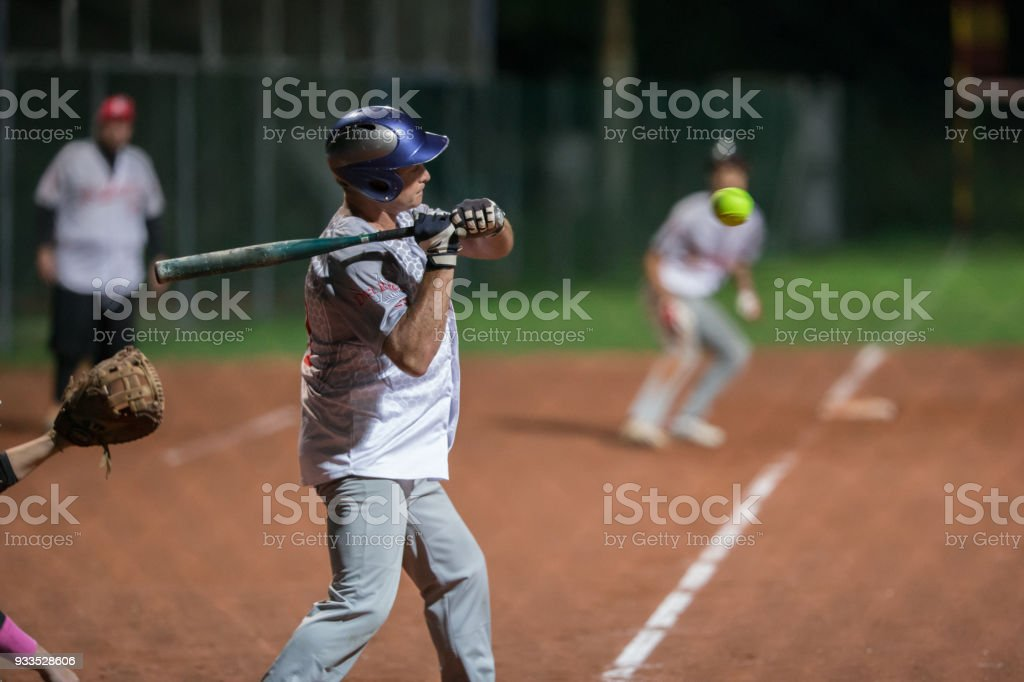 Softball Batter Trying to Hit the Ball Mid Air