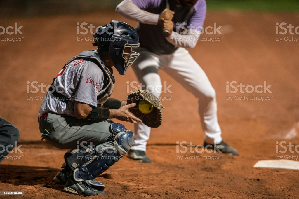 Softball Catcher Kneeling and Grabbing the Ball stock photo
