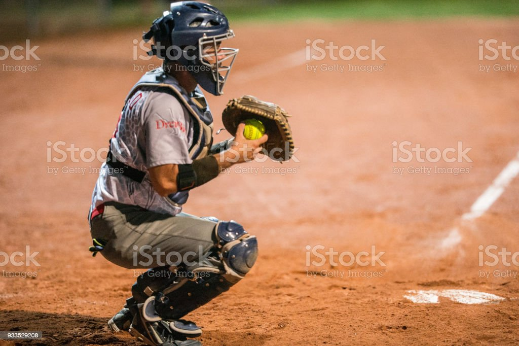 Softball Catcher Kneeling and Holding the Ball