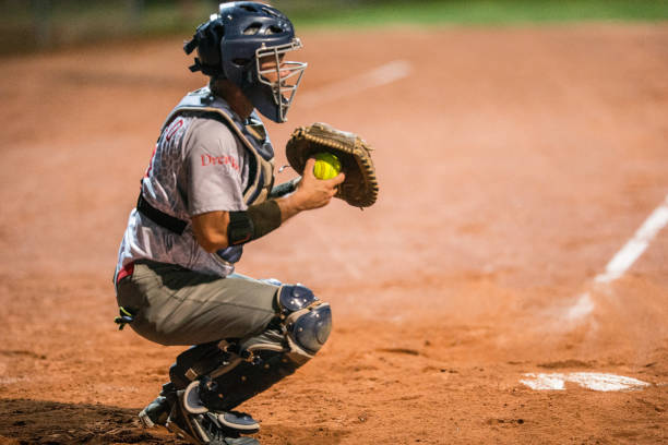 Softball Catcher Kneeling and Holding the Ball stock photo