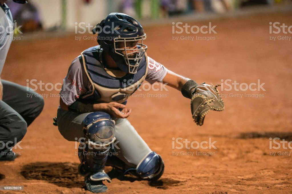 Softball Catcher on his Knees Preparing to Catch the Ball stock photo