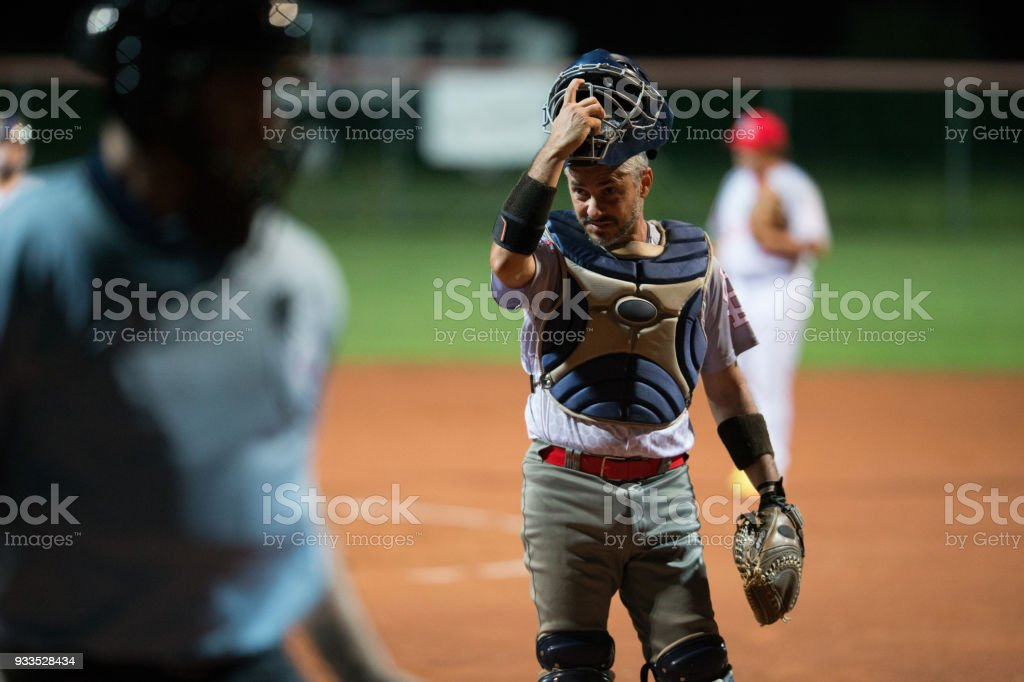 Softball Catcher Taking his Helmet Off stock photo
