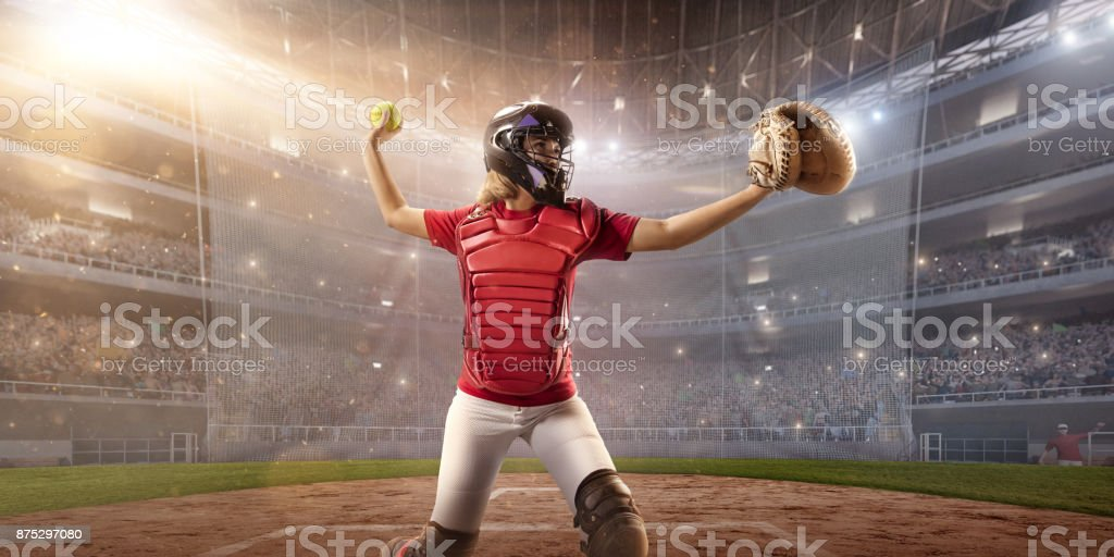 Softball female catcher on a professional arena. Beautiful athlete in...