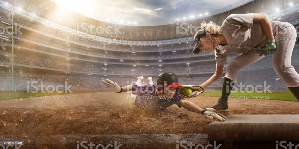 Softball female players on a professional arena. Baseball 3rd base...