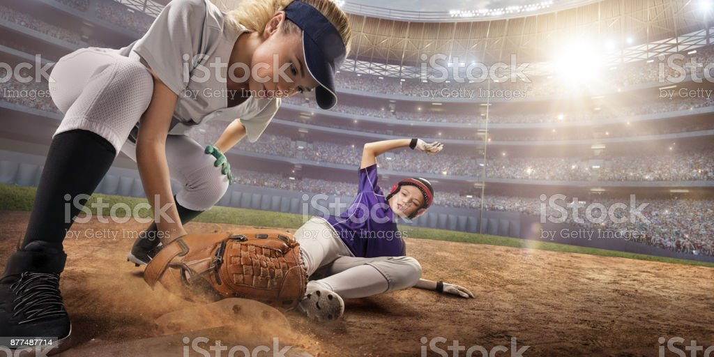 Softball female players on a professional arena. Baseball 3rd base...