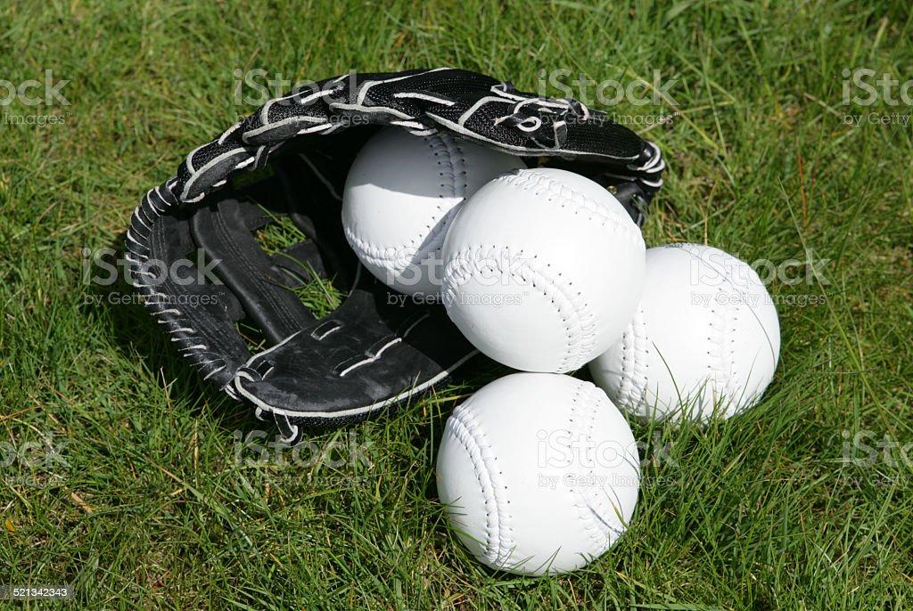 softball glove and balls on grass