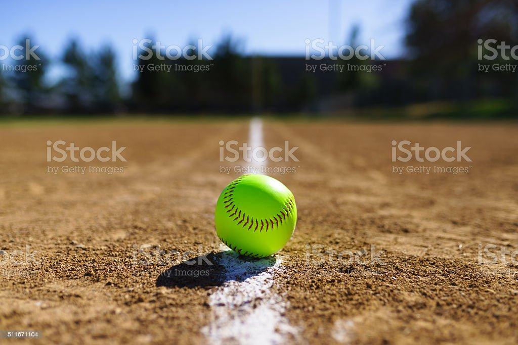 Softball on a white foul line in a softball field in California...