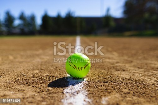 Softball on a white foul line in a softball field in California mountains