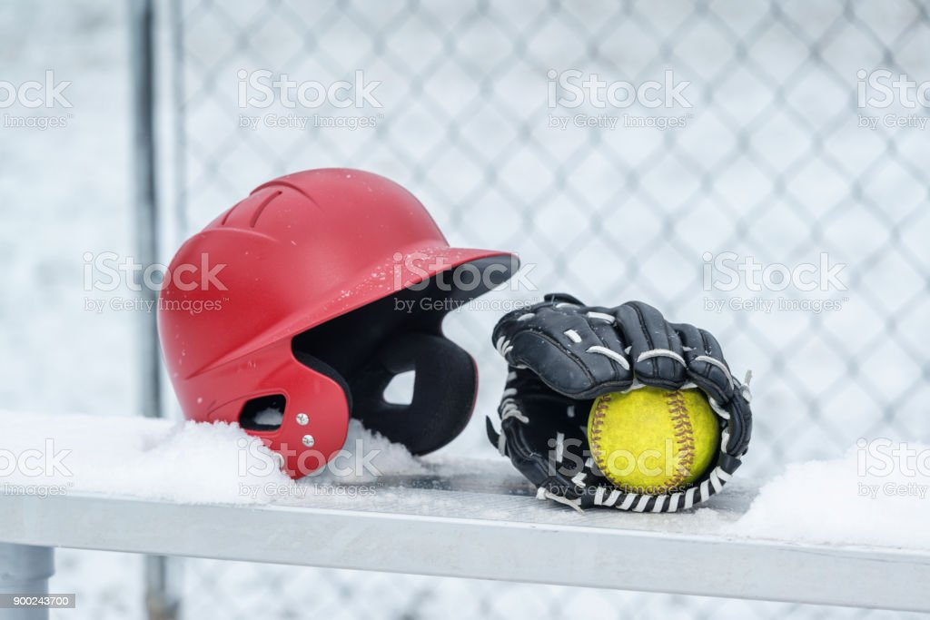 A yellow softball inside a black leather softball glove with white...