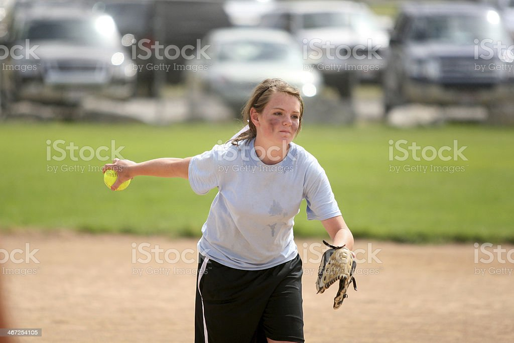 Girl pitching in a softball game.