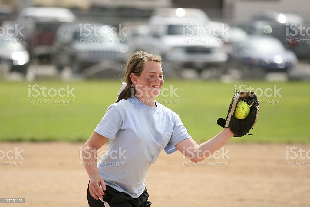 Girl catching a softball in a softball game.