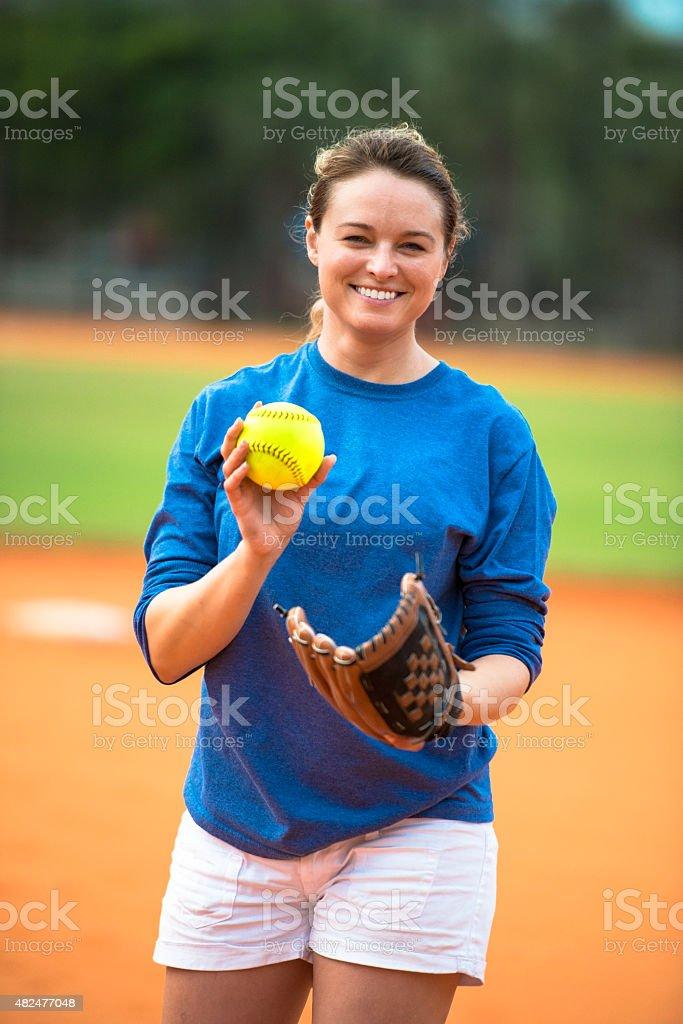 Young woman softball pitcher on baseball field