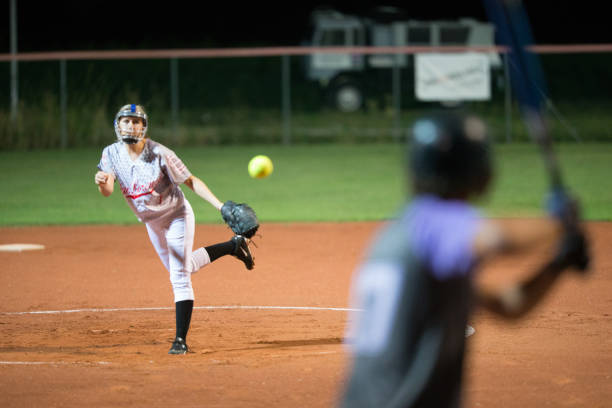 softball pitcher throwing the ball to batter - softball stock photos and pictures