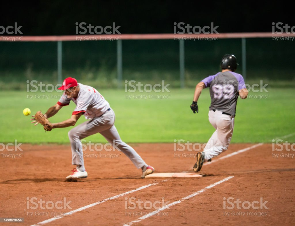 Softball Player Trying to Catch the Ball, Opponent Running Past Him