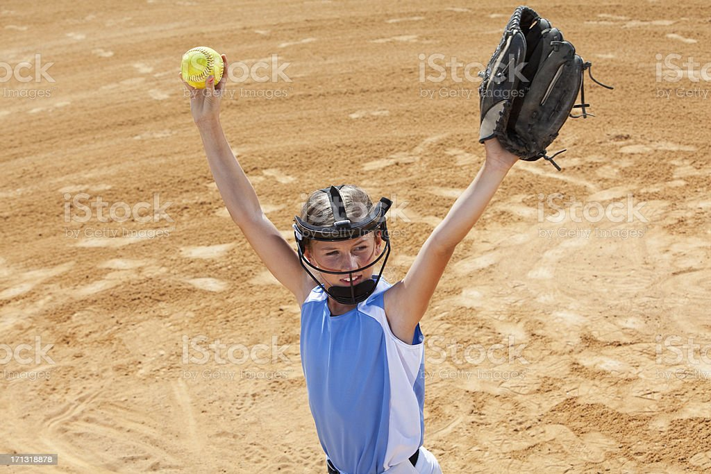 Softball player walking in from infield with arms raised stock photo