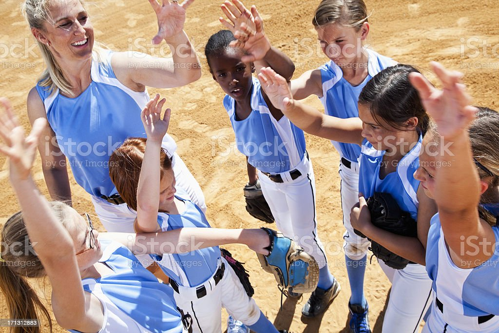 Softball players and coach doing team cheer royalty-free stock photo